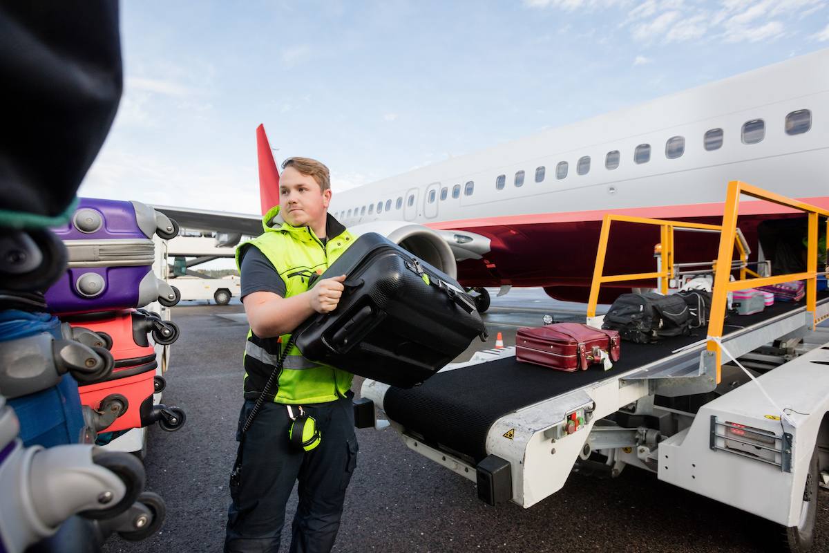 Mid adult male worker stacking bags on trailer at runway