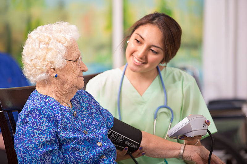nurse assisting an older woman