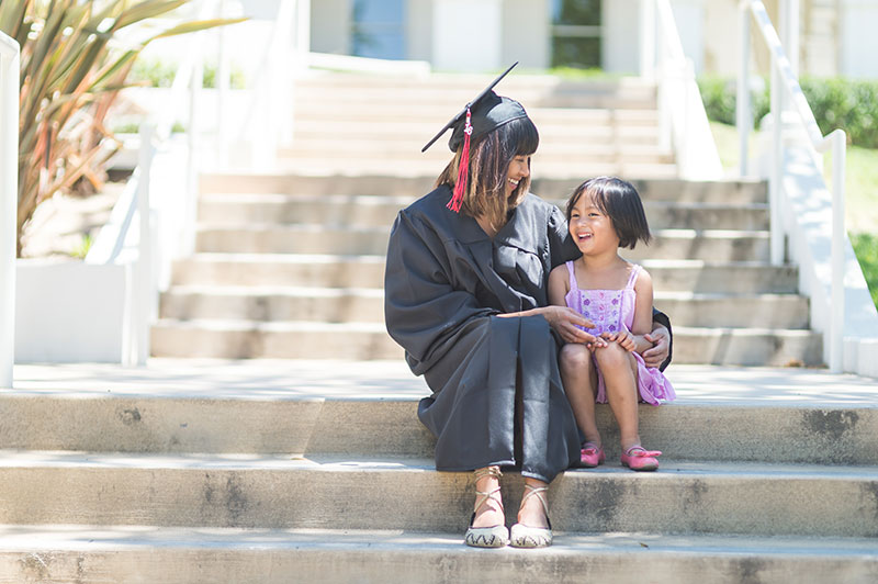 graduate student sitting next to a young child