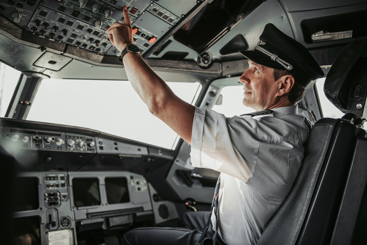 Man in uniform pushing button in cabin during flight stock photo. Airways concept